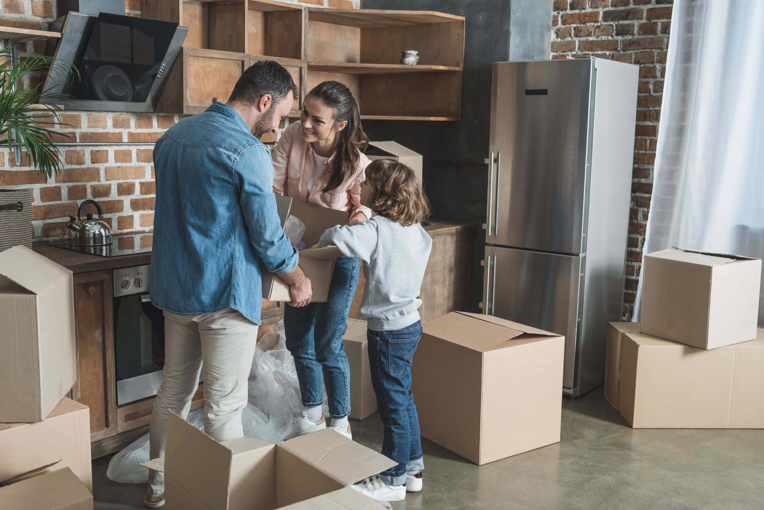 Happy Family Packing Cardboard Boxes While Moving