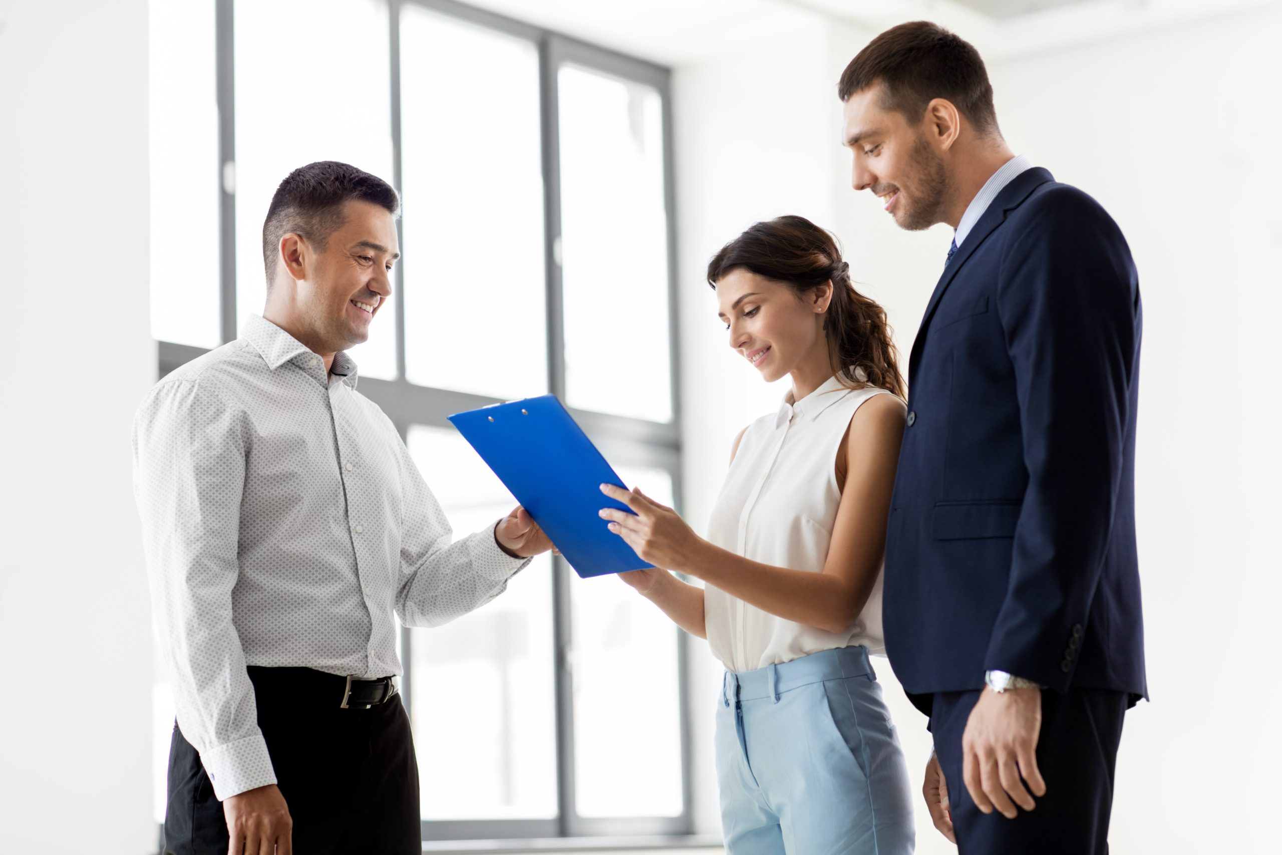 couple looking over paperwork with realtor