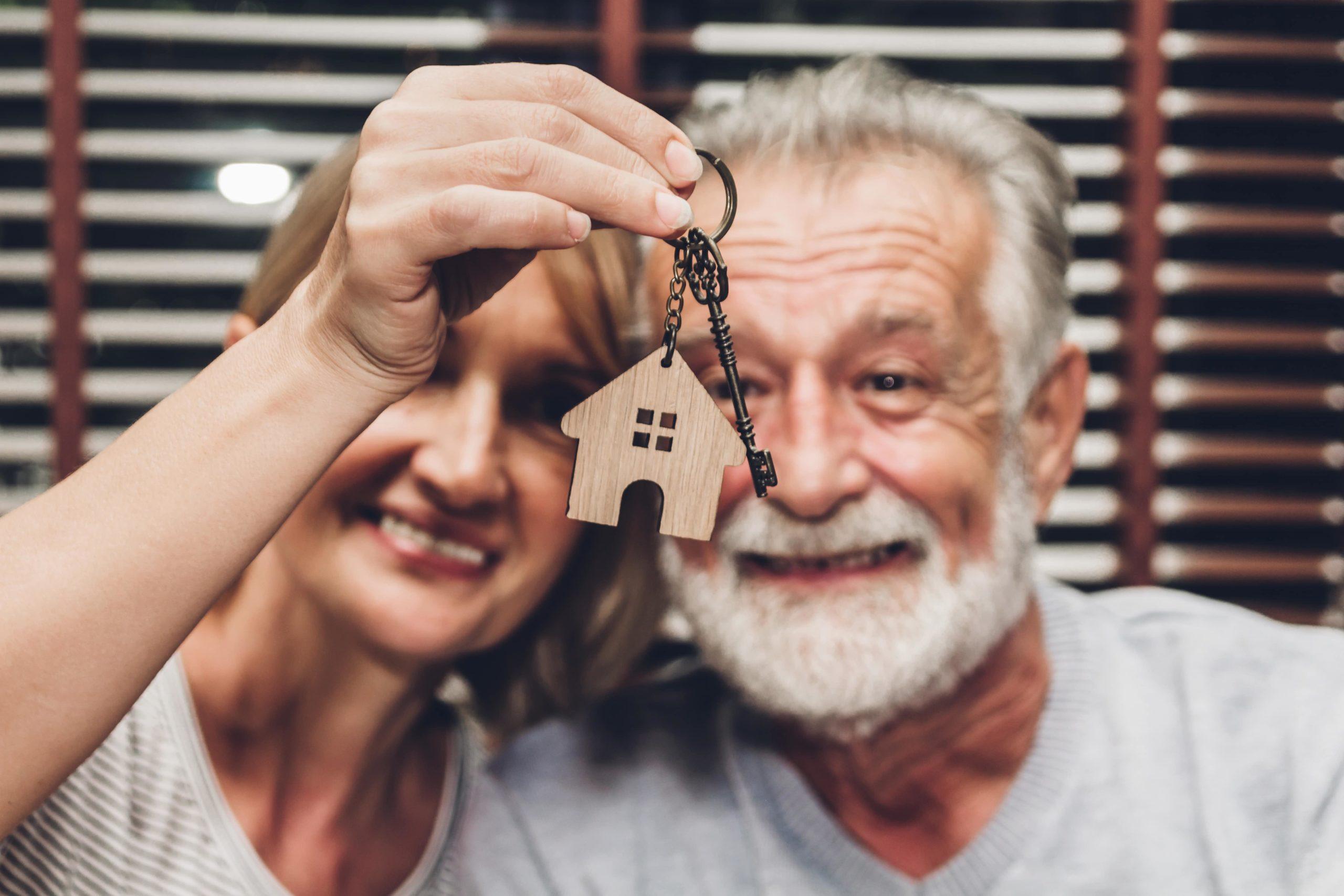 Elderly couple smiling with house key